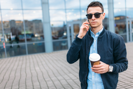 a man with a paper Cup of coffee, goes through the city, a handsome guy in stylish clothes and sunglasses, making a phone call, good weather Imagens