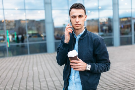 a man with a paper Cup of coffee, goes through the city, a handsome guy in stylish clothes, on the phone, good weather