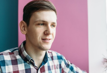 Handsome young man in a cell shirt, on a background of pink and blue wall, close-up, the guy is dreaming Stock Photo