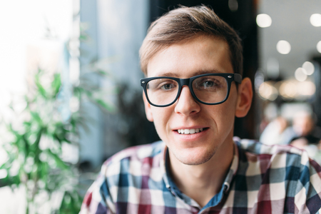Portrait of a young man in glasses and a shirt with a positive mood and a wide smile, stylish man Stock Photo