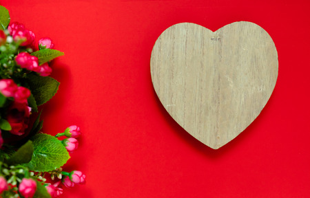 Valentines day gift for the second half, a bouquet of flowers, a romantic photo, a wooden heart on a red background, background suitable for advertisement , insert text,love Stock Photo