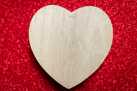 a sparkling red background, rhinestone,Valentine's Day gift for the second half, a romantic photo, a wooden heart on a red background, suitable for text insertion, ads Foto de archivo