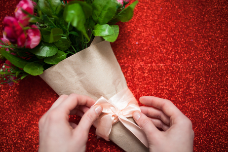 Valentines day,florist woman packs a bouquet of flowers of roses in a paper wrapper with a bow on wooden table, suitable for advertisement, insert text