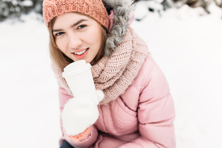Portrait of a beautiful young girl in white knitted mittens, outdoors, holding a paper Cup with a hot beverage, bright winter day.the woman smiles and is happy, close-up, Trees in first snow in the background.