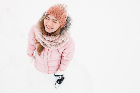 Girl posing outdoors, a woman looks up smiling and happy young woman in ski clothes outdoor recreation in cold weather ,image for advertising,insert text