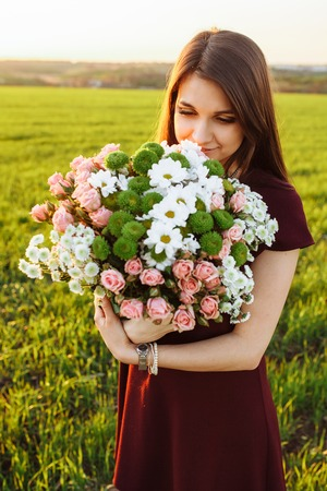 young, happy, girl, posing with a big bouquet, against the sunset on the field Stock Photo