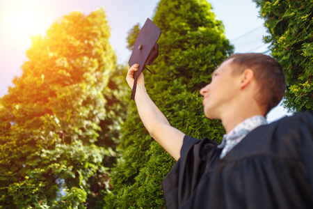 The successful graduate guy , in academic gowns, raised graduation cap, goodbye school , can be used for advertisement,