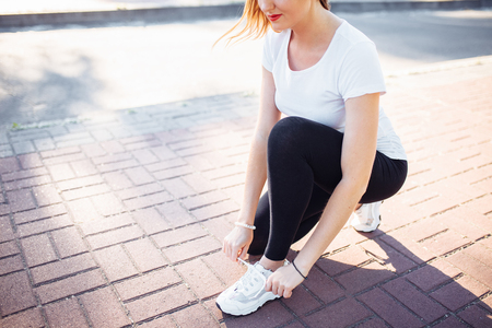 Young athletic girl, tying shoelaces, before Jogging, can be used for advertising,
