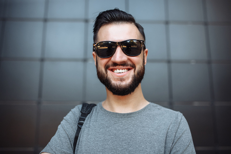 Portrait of a beautiful stylish guy, hipster with glasses, dressed in a gray empty t-shirt, standing on a black wall background.