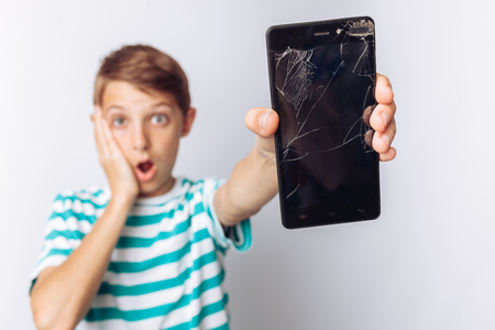Portrait of a beautiful and emotional boy, in whose hands a broken phone shows surprise, white background, blue t-shirt,