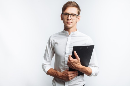 Portrait of a young attractive guy in glasses, in a white shirt, with a folder in his hands, isolated on a white background, Stock Photo