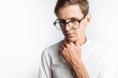 Portrait of young attractive guy in glasses, in white shirt, isolated on white background,