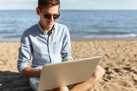 Young guy with glasses, working on his laptop on the beach, work on vacation, 스톡 콘텐츠