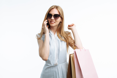 Young beautiful girl in glasses posing with phone, with shopping, on white background, with gift bags, talking on phone and smiling,