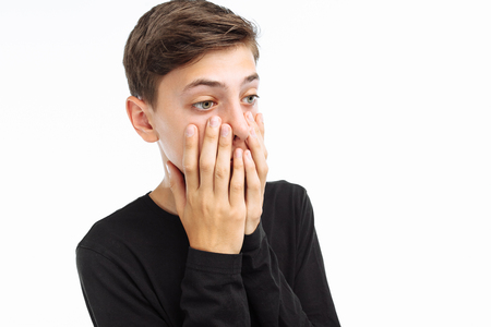 Photo emotional teenager, guy in black t-shirt, shows the emotions of fear, closing his mouth with his hands, on a white background,