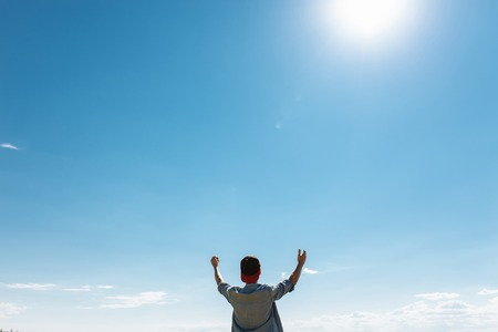 the man raised his hands to the sky, against the blue blue sky, the guy in the cap and shirt