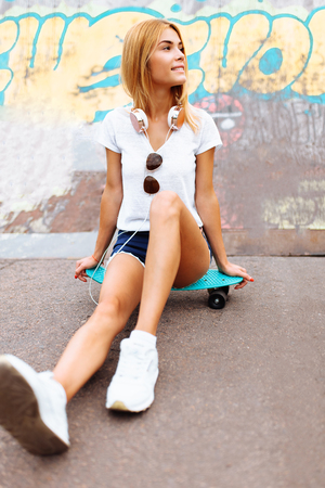 portrait of a beautiful girl, with a skate, in a skate Park