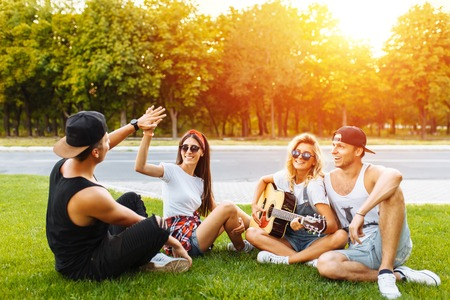 Company of friends having fun at sunset sitting on the grass, playing guitar, good summer mood