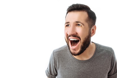 Portrait of cheerful and surprised man with beard, in grey t-shirt, looking at camera, isolated on white background, advertisement, text insertion