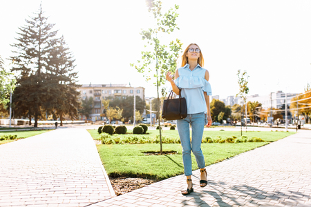 Young positive beautiful girl with glasses, student strolling in the Park, in a good mood