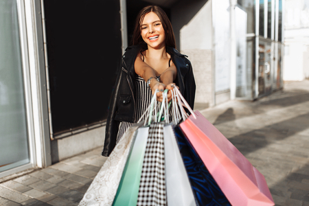 Young girl enjoying a successful shopping, walking down the street, showing their purchases in the camera