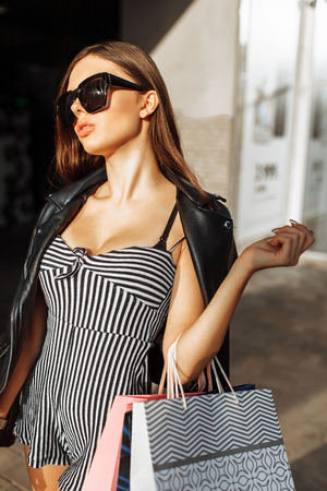 Beautiful stylish girl in sunglasses walking down the street, after shopping, holding bags in her hands, posing outdoors