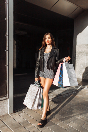 Beautiful stylish girl walking down the street, after shopping, holding bags, outdoors Stock fotó