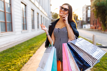 A young girl enjoys a successful shopping, on the background of a beautiful sunset, talking on the phone, bags in hand