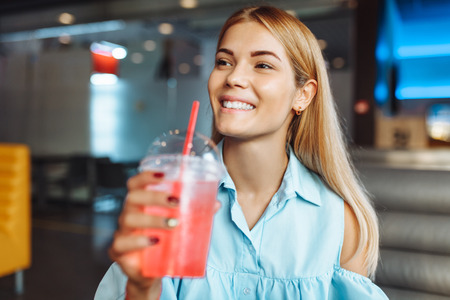 Beautiful young cheerful girl, drinking a cocktail, sitting in a cafe and waiting for someone Zdjęcie Seryjne