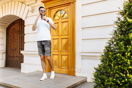 Stylish hipster with a beard and a white shirt on the background of a white building talking on the phone and drinking coffee