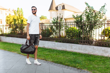Stylish hipster with a beard in a white t-shirt, sunglasses, with a bag in his hands walking around the city
