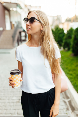 Portrait of a young woman wearing sunglasses, wearing a white t-shirt, outdoors and holding a Cup of coffee. Girl walking around the city and drinking coffee.