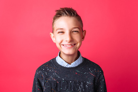 Positive teenager, smiling broadly, on a red background
