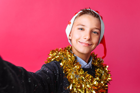 Teen guy makes a selfie in the hat of Santa Claus and tinsel on the neck, on a red background. 版權商用圖片