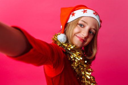 The girl makes a selfie in the hat of Santa Claus and tinsel on the neck, a schoolgirl on a red background.