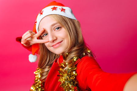 The teen girl shows a greeting gesture and takes a selfie in Santa's hat and with tinsel around her neck on a red background. 版權商用圖片
