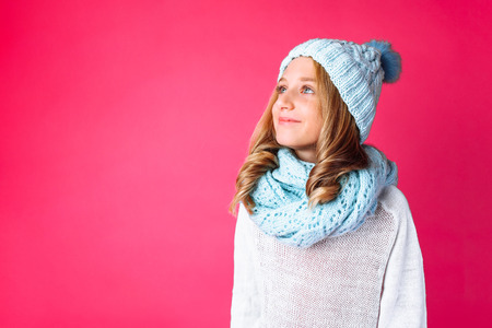 cute teenage girl in white sweater standing isolated on pink background wearing warm blue hat and warm scarf.