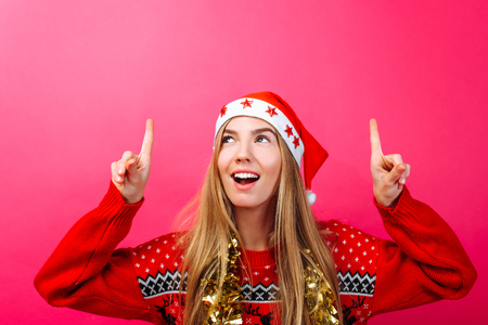 Beautiful surprised girl in Santas hat, with tinsel on her neck pointing fingers up and showing a blank copy space on a red background. Stok Fotoğraf