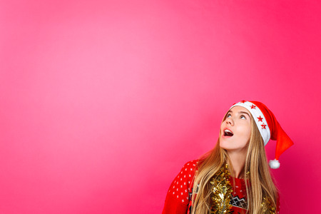 A beautiful surprised girl in Santas hat, with tinsel on her neck, looks at the empty copy space on a red background. Stok Fotoğraf