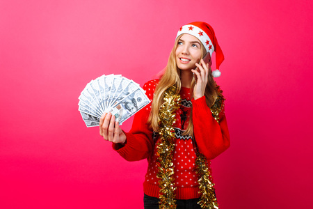 Happy girl in red sweater and Santa hat, talking on phone and holding money, on red background. Stock fotó