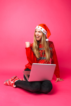 Happy girl in red sweater and Santa hat, excited about the good news, shocked girl shows a success victory gesture, on red background.