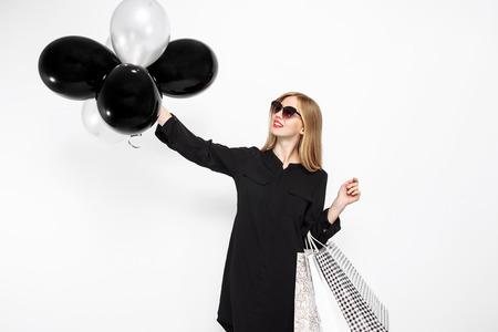 happy woman in sunglasses in black dress and with red lips holding bags and black balls, satisfied girls after shopping, Black Friday on white background Stock Photo