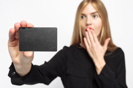 Shocked girl in black dress and with red lips, holding credit card, white background, black Friday, shopping, money