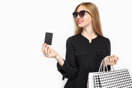 black Friday. Elegant girl in black dress and with red lips, holding bags, for shopping, and credit card on white background