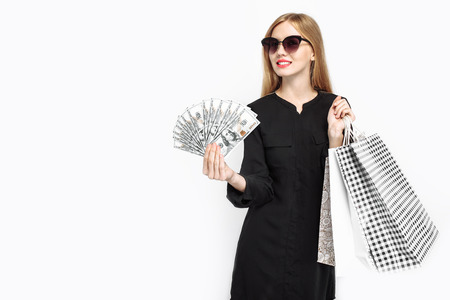 Elegant girl in black dress and with red lips, holding packages and money getting ready for Black Friday. Black Friday, discounts, shopping Stock Photo