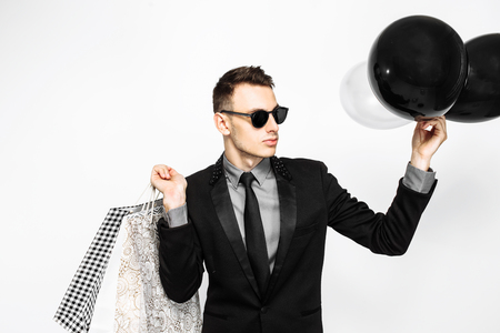 An elegant guy in a black suit and sunglasses, with shopping bags and balloons, is waiting for black Friday, on a white background. Black Friday, shopping, discounts
