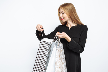 Elegant girl in black dress and with red lips, with bags, for shopping, happy after a successful shopping, Black Friday, discounts,