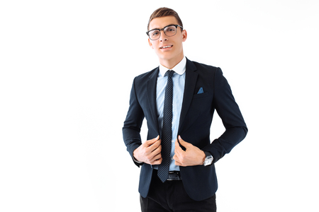 Elegant young handsome man, in suit and glasses, posing on white background