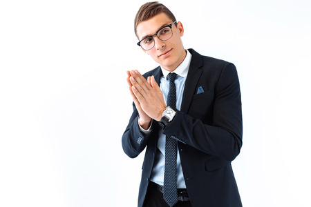 A business guy in glasses and a suit, rubbing his hands, a cunning handsome plans his cunning plan on a white background.