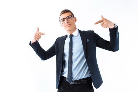 Confident businessman in glasses and suit, man shows his fingers on himself standing isolated on white background. A handsome businessman is glad that he managed to make a deal